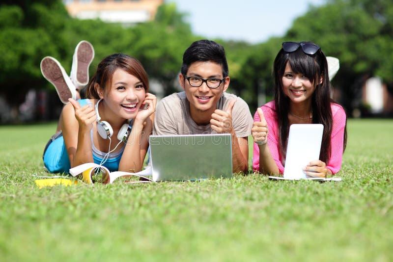 使用计算机的愉快的大学生 免版税库存照片