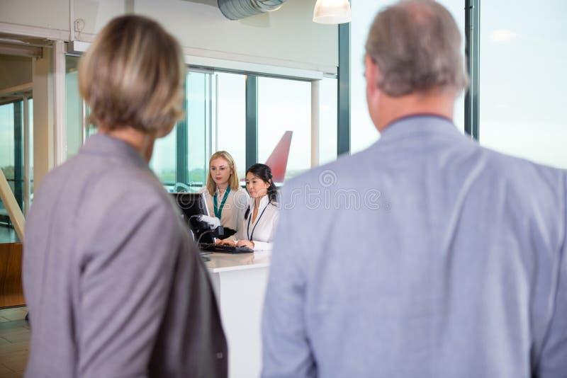 使用计算机的接待员,当资深企业夫妇Waitin时 图库摄影