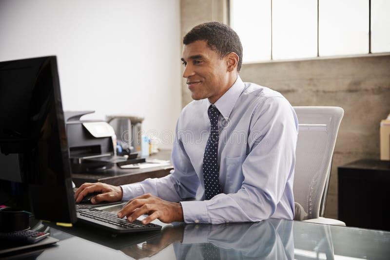 使用计算机的混合的族种商人在办公室 免版税图库摄影