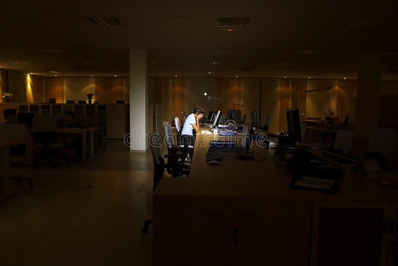 使用计算机的疲乏的妇女在黑暗的办公室 免版税库存照片