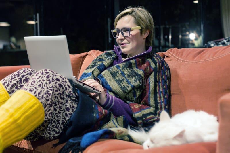 使用计算机的舒适家庭内部和妇女与猫一起 免版税库存图片