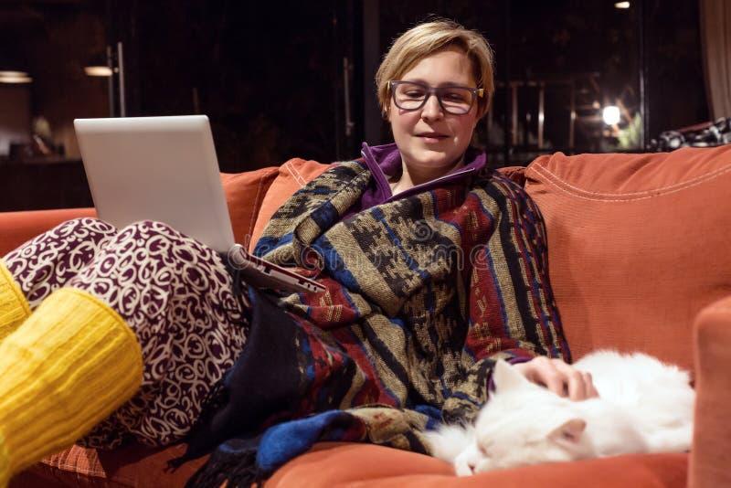 使用计算机的舒适家庭内部和妇女使用与猫 免版税库存图片