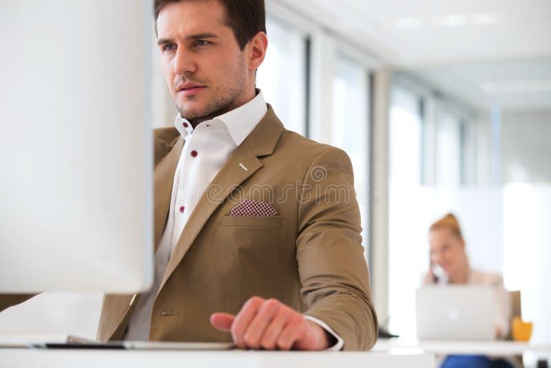使用计算机的英俊的年轻商人在有女性同事的办公室在背景中 库存图片
