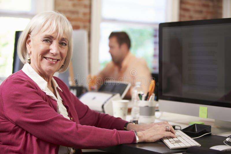 使用计算机的资深女实业家在创造性的办公室 库存图片
