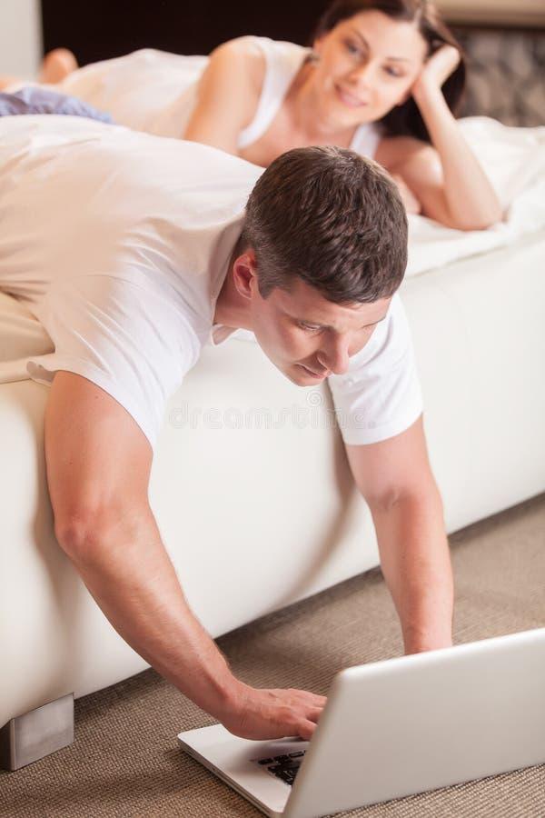 使用计算机的年轻人在床 免版税库存照片