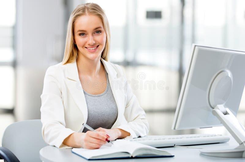 使用计算机的年轻女商人在办公室 免版税库存照片