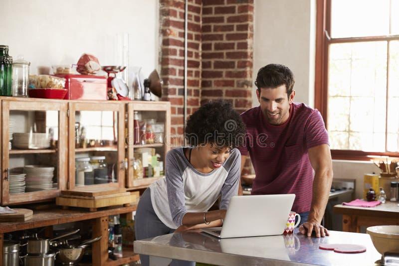 使用计算机的年轻混合的族种夫妇在厨房里 库存图片