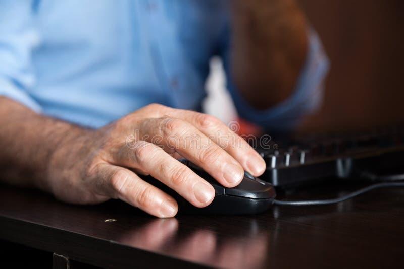 使用计算机老鼠的人在书桌在类 图库摄影