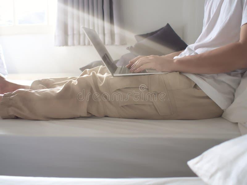使用计算机膝上型计算机的年轻人的播种的图象在客厅 库存图片