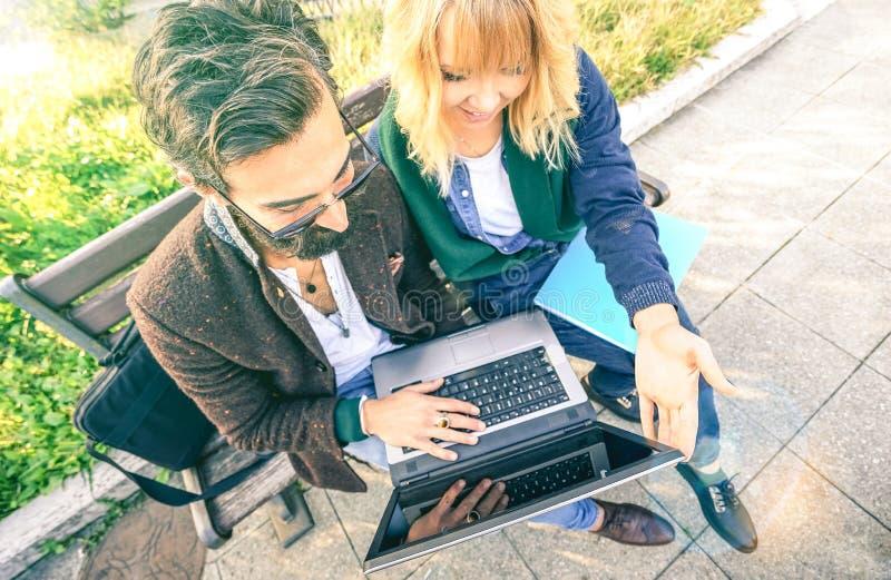 使用计算机膝上型计算机的年轻行家夫妇在都市室外地点-与millenials的现代乐趣概念在新的趋向和 库存照片