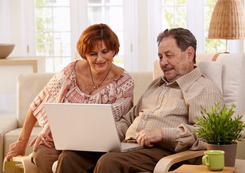 使用计算机计算机的年长夫妇 库存照片