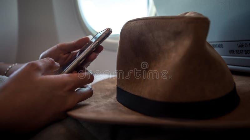 使用设备电话的亚裔妇女乘客在飞行内部飞机期间 免版税图库摄影