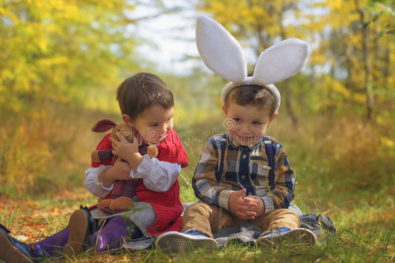 使用象兔宝宝的两个小孩在公园 免版税库存照片