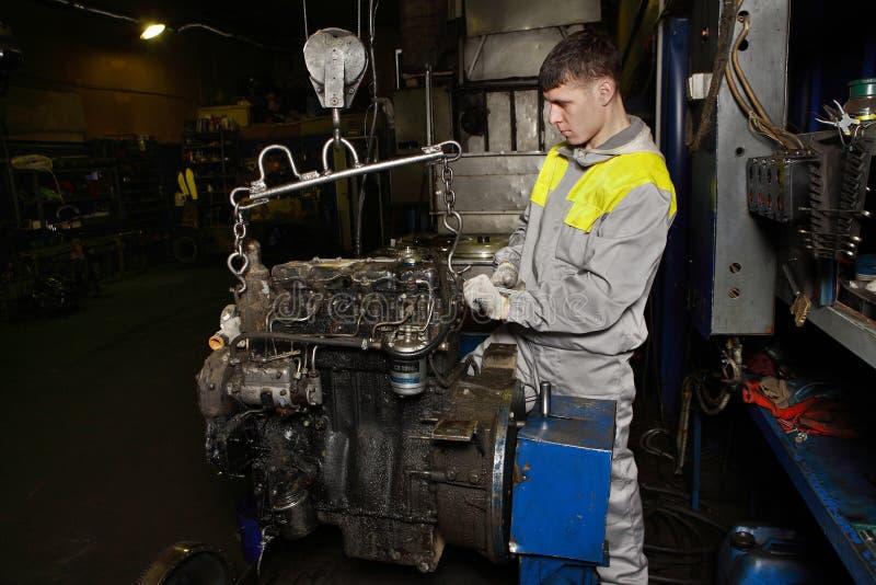 使用起重机,汽车机械师举了引擎卡车 库存图片