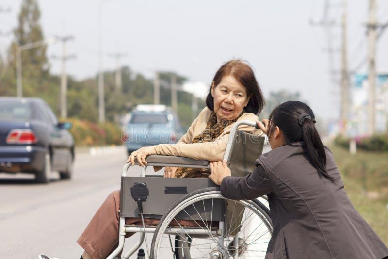 使用轮椅十字架街道的资深妇女 免版税库存照片