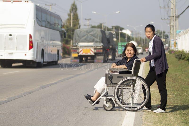 使用轮椅十字架街道的资深妇女 免版税库存图片