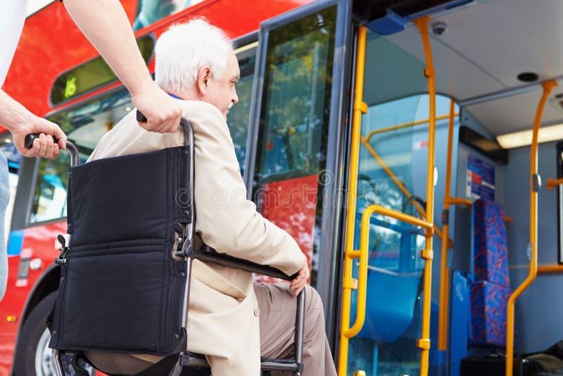 使用轮椅进路坡道的资深夫妇搭乘公共汽车 免版税图库摄影