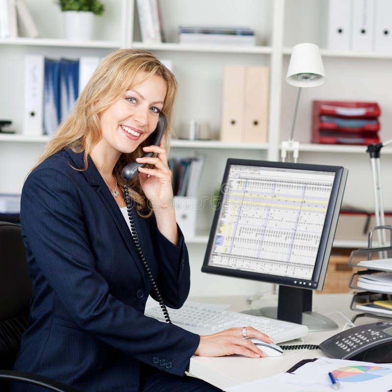 使用输送路线电话的确信的女实业家在书桌 库存图片
