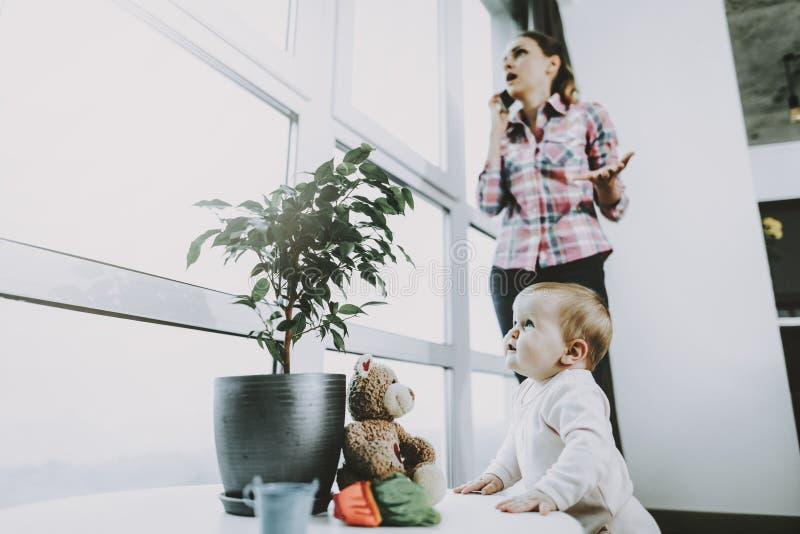 使用逗人喜爱的婴孩,当年轻母亲打电话时 免版税库存图片