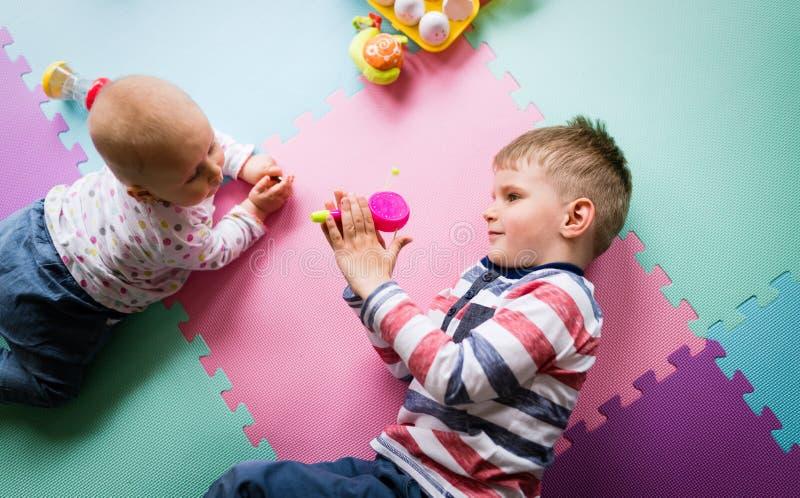 使用逗人喜爱的小孩,当坐地毯时 图库摄影