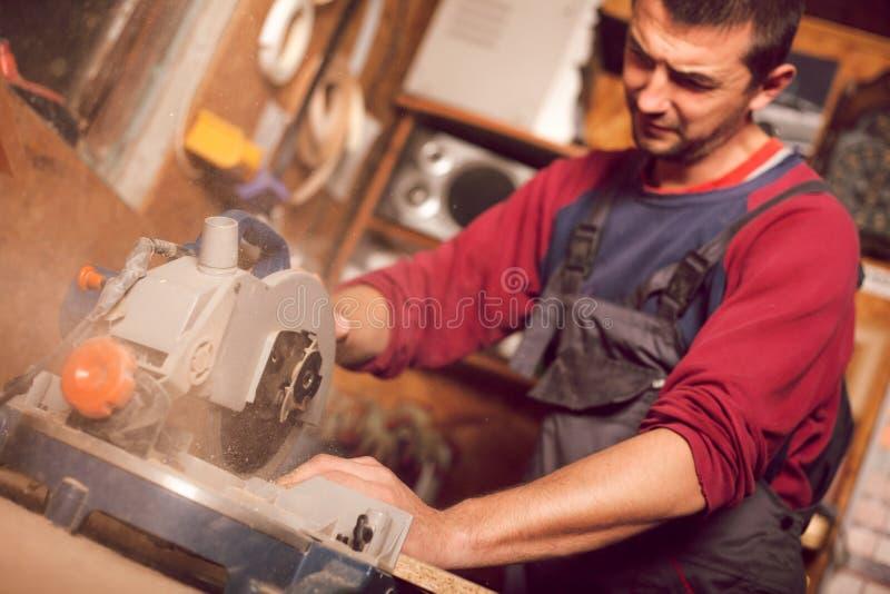 使用通报的木匠为削减木板看见了 免版税库存照片