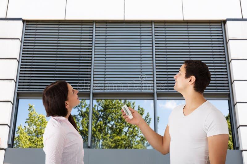 使用遥控的夫妇对开窗口快门 免版税库存图片