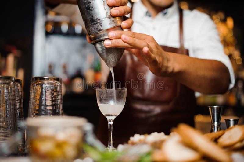 使用酒吧设备,男服务员我混合一个白色鸡尾酒 库存图片
