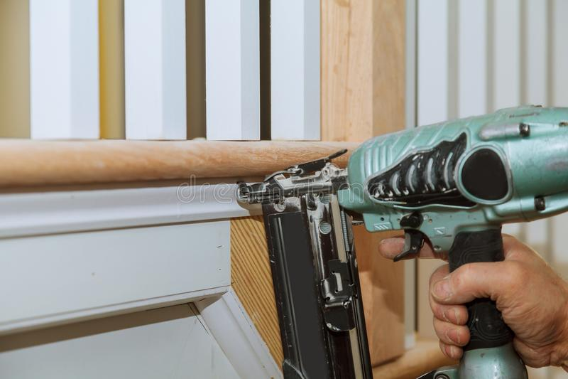 使用钉子枪的кCarpenter曲头钉对铸造的修剪,与警告标记那所有电动工具 免版税库存图片