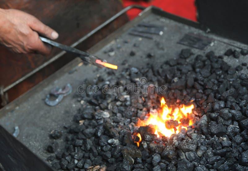 使用钳子塑造热的铁一位更老的铁匠的手 库存照片