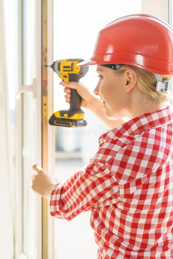 使用钻子的妇女固定或安装窗口 免版税库存图片