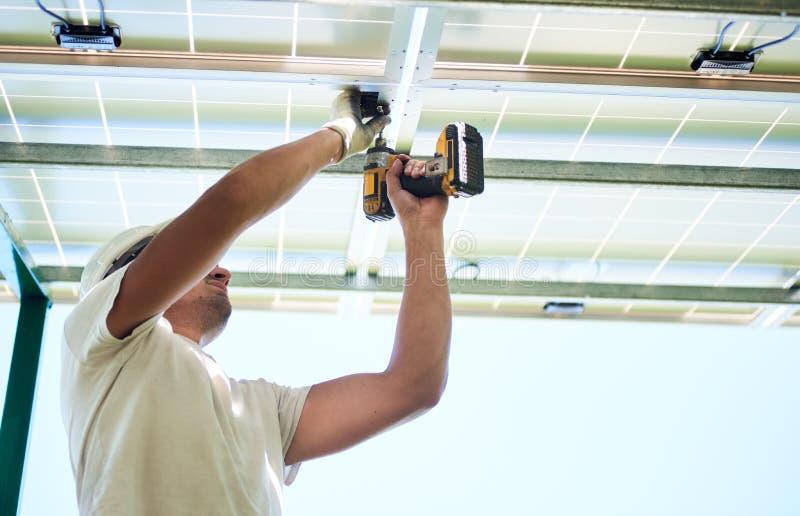 使用钻子的工作者照片通过太阳电池板安装 免版税库存照片