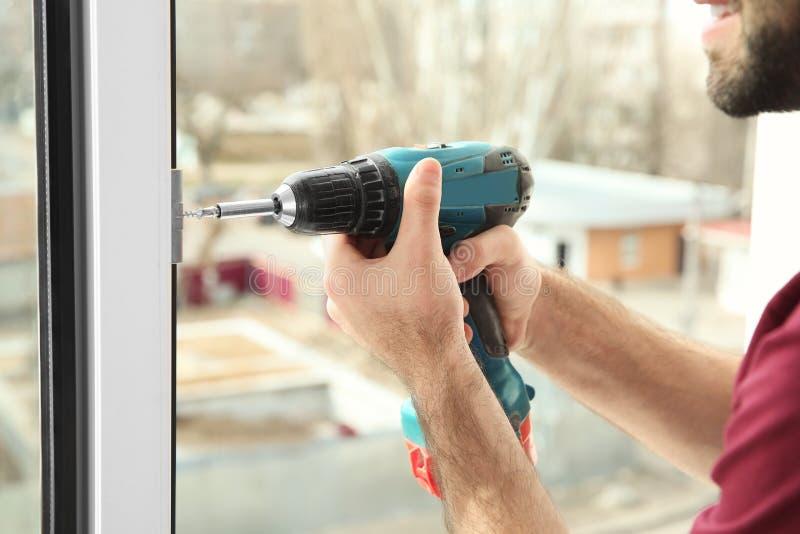 使用钻子的建筑工人,当安装窗口户内时 免版税库存照片
