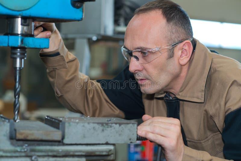 使用钻床的成熟人在工业工厂 免版税库存照片