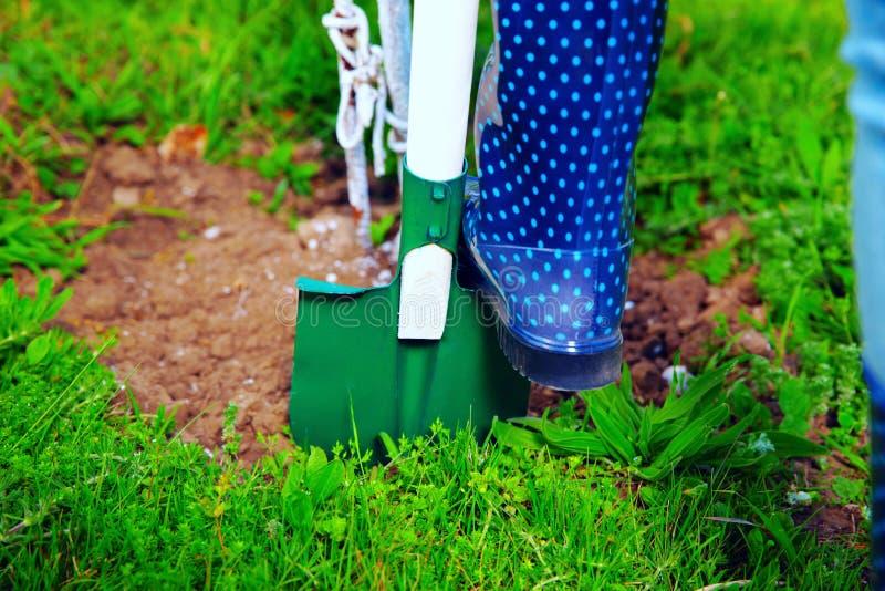 使用铁锹的妇女在她的庭院 库存照片