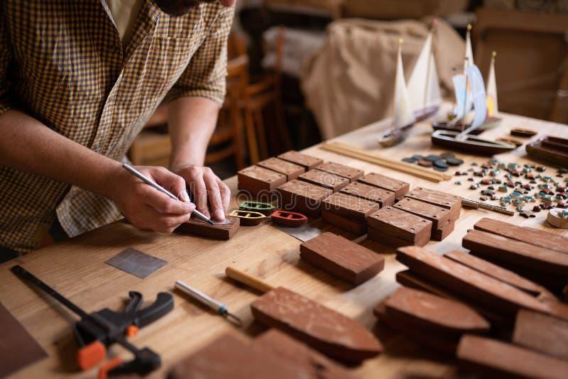 使用铅笔的特写镜头观点的木匠应付小船形状在木头的 免版税库存图片
