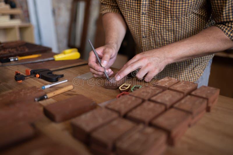 使用铅笔的特写镜头观点的木匠应付小船形状在木头的 免版税图库摄影