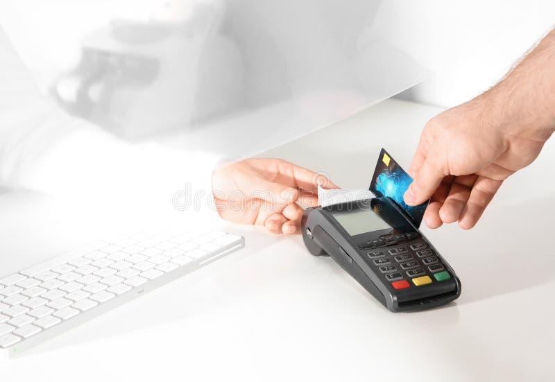 使用银行终端的人为信用卡支付在出纳处窗口 免版税图库摄影