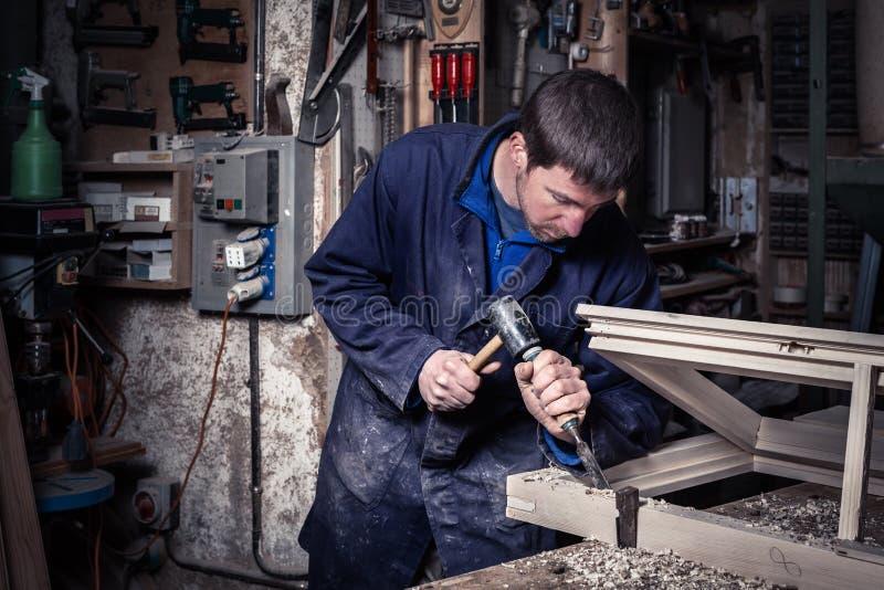 使用锤子和凿子的木匠在车间 免版税库存图片