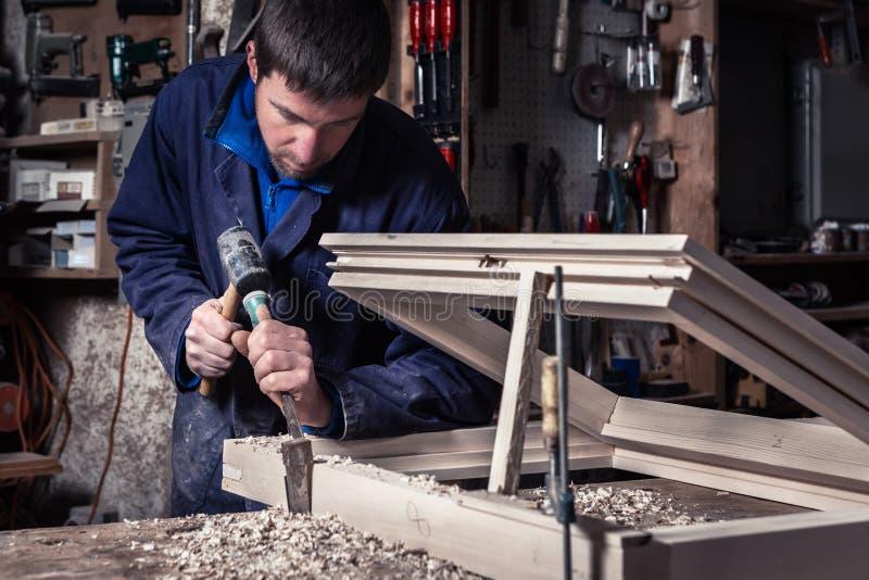 使用锤子和凿子的木匠在车间 库存照片