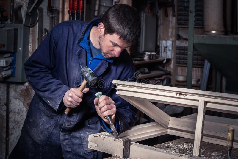 使用锤子和凿子的木匠在车间 免版税图库摄影