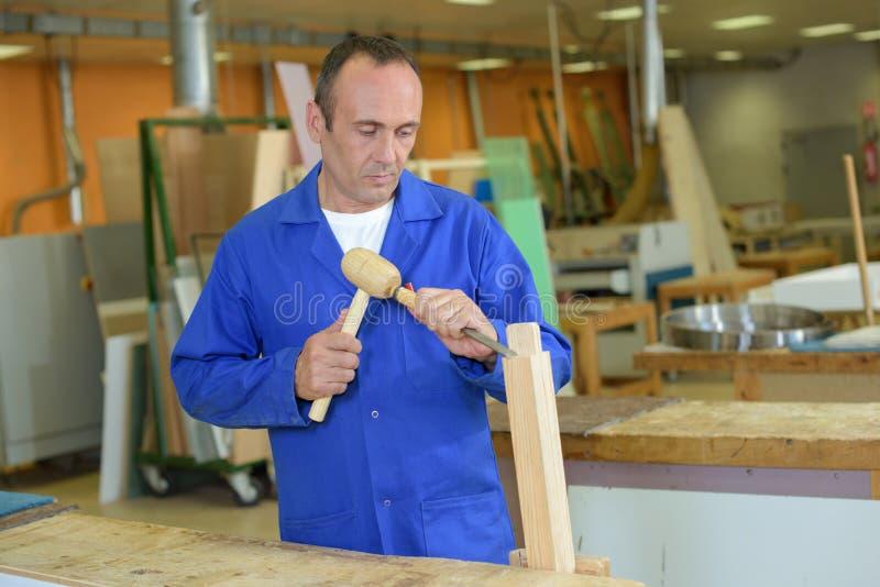 使用锤子和凿子的木匠 免版税库存图片