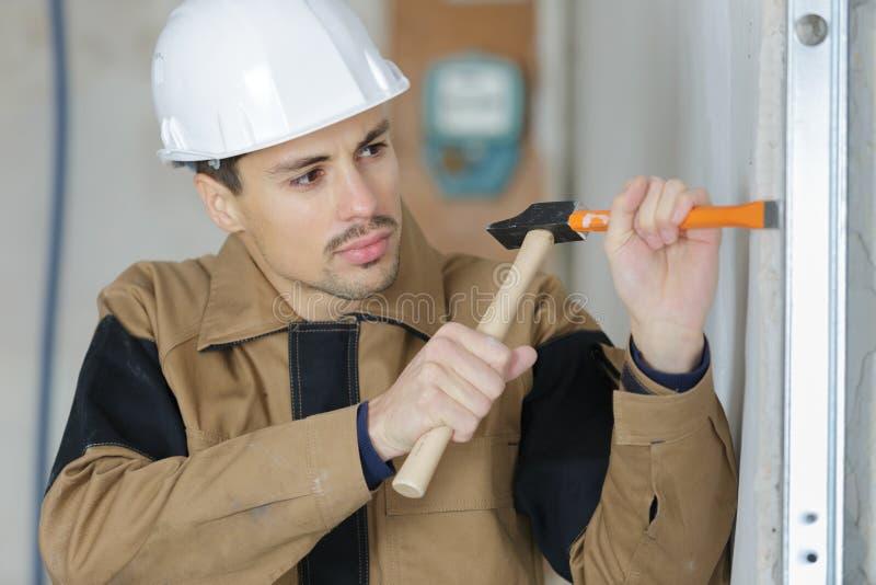 使用锤子和凿子的Constructon工作者 免版税库存照片