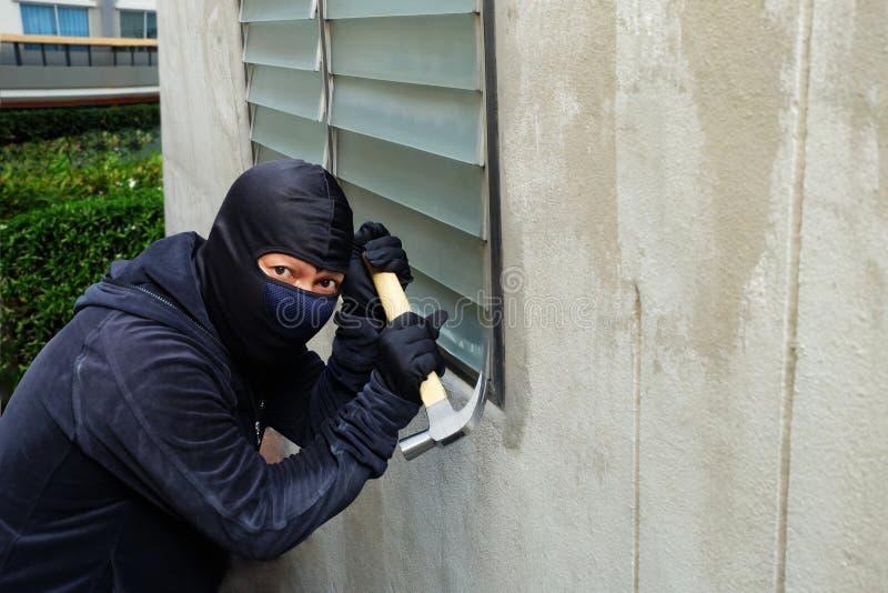 使用锤子的被掩没的窃贼设法打碎窗口 免版税库存图片