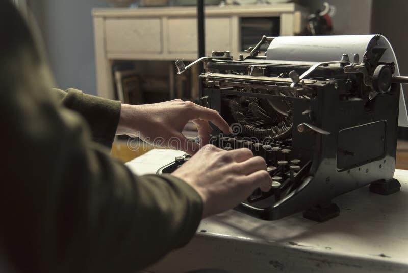 使用键入的减速火箭的打字机机器工作作家的人 免版税库存图片