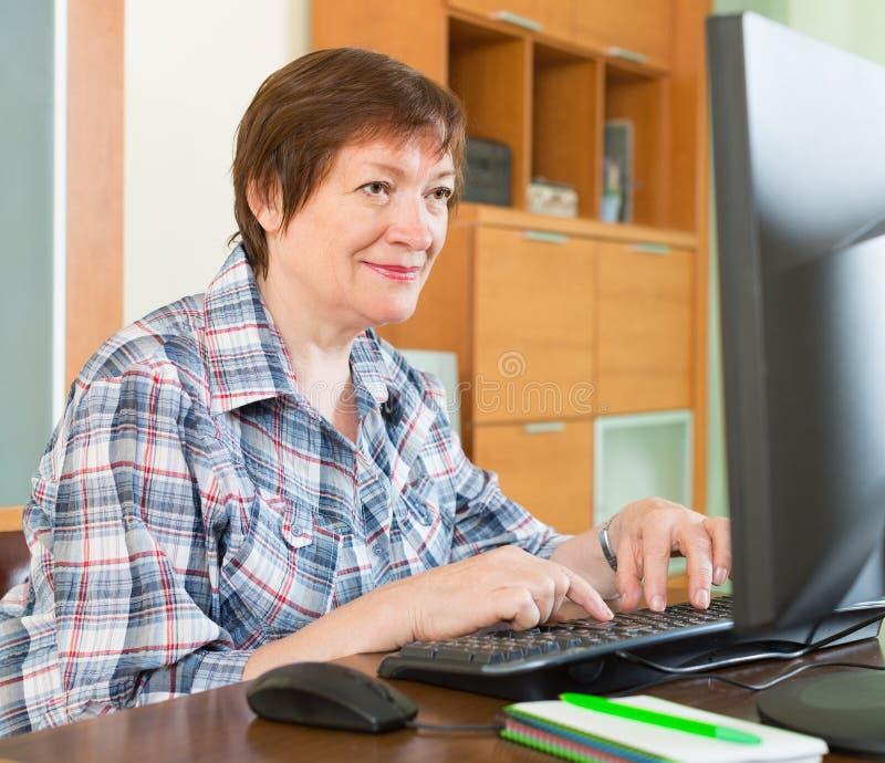 使用键盘的微笑的资深妇女 免版税库存照片