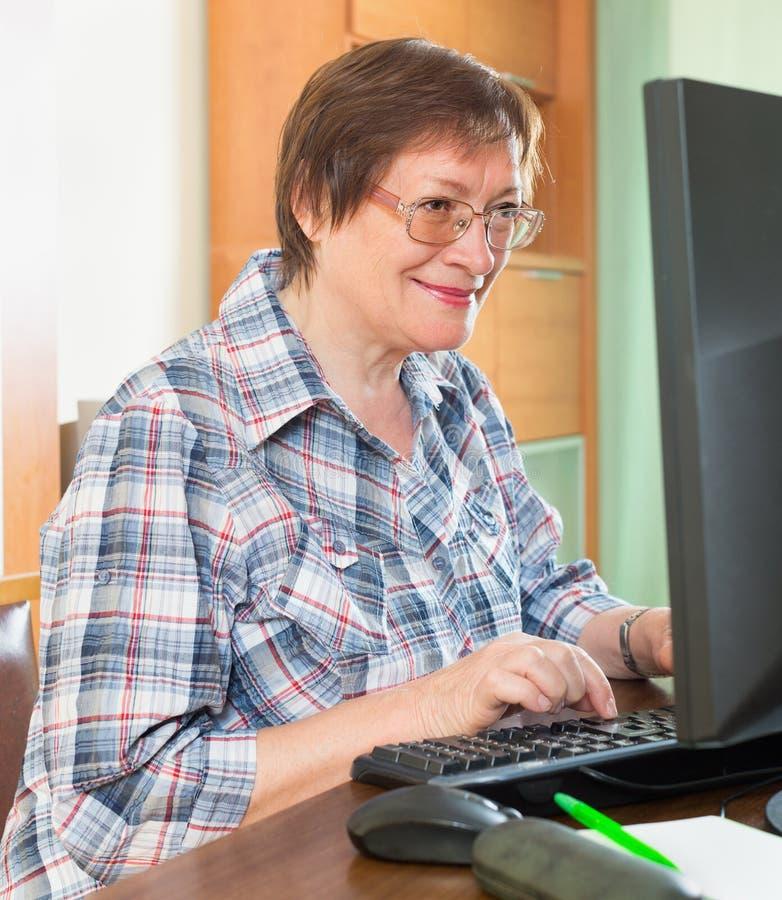 使用键盘的微笑的资深妇女 图库摄影