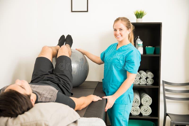使用锻炼球的理疗师为耐心` s腿Workou 库存图片