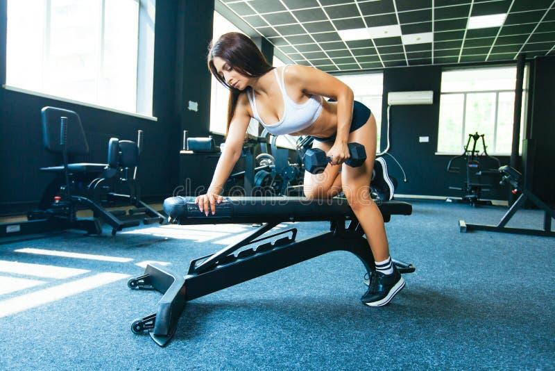 使用长凳,女孩执行一个哑铃单手在倾斜 在最宽广的背部肌肉的锻炼与 免版税库存图片
