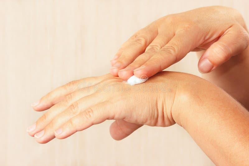 使用防皱护肤霜的女性手 免版税图库摄影