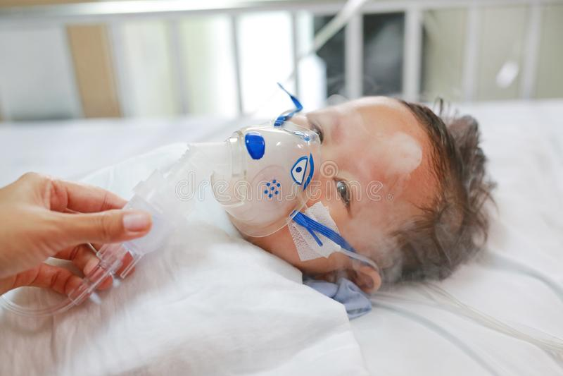 使用雾化器的小孩男孩治疗哮喘或肺炎疾病 患者的病态的男婴基于供并且有吸入疗法住宿 库存照片